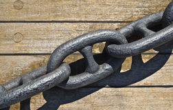 Iron chain for boats anchor. On a wooden plan stock images