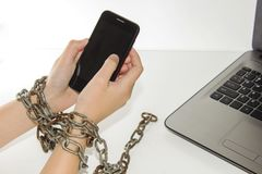 Iron chain ties together hands and smartphone - mobile phone addiction concept. Iron chain ties together hands and smartphone - mobile phone addiction concept Royalty Free Stock Image