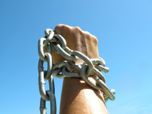 Iron chain in woman's fist. In front of blue sky Royalty Free Stock Image