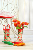 Iron chair with little rain boots and tulips Stock Photo