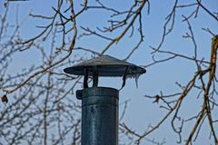Iron chimney pipe against the sky and branches. Gray iron pipe chimney against the sky and branches Stock Photo