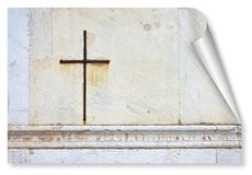 Iron Christian cross snuggled against a white stone on a italian facade church - curl and shadow design concept image with copy. Space stock photography