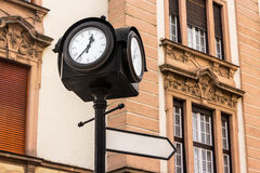 Iron city clock with index sign in europe. Iron city clock on a column with index sign on old european architecture background Stock Photo