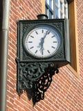 Iron clock. Vintage cast-iron clock on a sunny wall stock photos