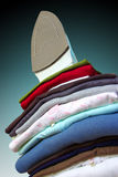 Iron and Clothes. Pile of assorted clothes and iron against blue and black background Stock Photography