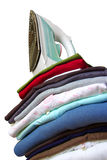 Iron on Clothes. Pile of assorted clothes and iron isolated in white background Stock Photo