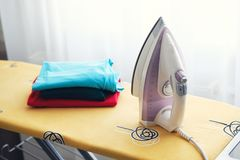 Iron and clothes on the Ironing Board in the apartment. Close up stock photos