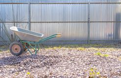 Gardening Tools. Iron wheelbarrow on the rubble stock photos