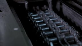 Iron conveyor chain moves in the old machine. Close up - iron conveyor chain moves in the old machine. Concept of production of iron parts in a small workshop stock video footage
