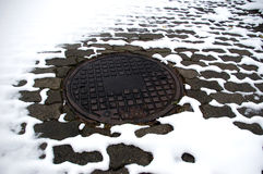 Iron cover. Of central heating canal and melting snow around royalty free stock image