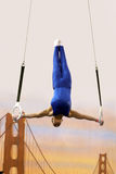 Iron cross. Gymnast competing on rings Royalty Free Stock Images