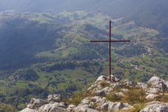 Iron cross above valley. Red iron cross on top of a rock, above a vast valley in Transylvania, Romania stock photos