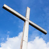 Iron cross in a cloudy sky. Iron cross over a blue sky with clouds background. Universal symbol of God and of faith. Belief or resurrection. Easter Stock Photo