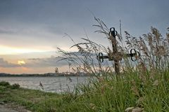 Iron cross at the edge of a lake. Covered with grass and the sunset royalty free stock image