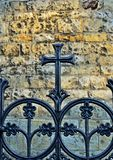 Minimalist Prague - Iron cross. Iron cross in front of stone wall, colored royalty free stock image