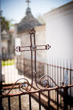 Iron cross in New Orleans cemetery. Cemetery in New Orleans with above ground graves and wrought iron cross stock photography