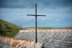 Iron cross. On the roof gable of St Enodoc Curch near Daymer bay in north Cornwall stock photo