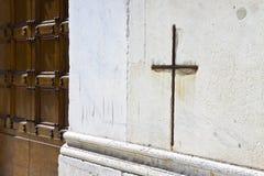 Iron cross snuggled in white stone on a italian facade church Stock Photos