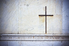 Iron cross snuggled in white stone on a italian facade church Stock Images