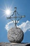 Iron cross on a stone ball, bright sunshine Stock Image