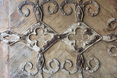 Iron decoration on the door. Iron decoration on an old wooden door stock photography