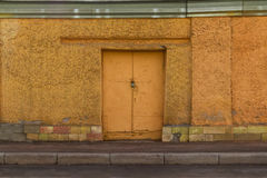 Iron door in the concrete wall. Locked iron door in yellow concrete wall front view Royalty Free Stock Image