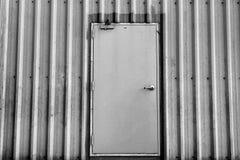 Iron door on corrugated metal sheet, black and white photo Stock Photo
