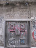 Iron door. Gray iron door locked with a big locker, with coloured graffiti, surrounded by grey wall Royalty Free Stock Photos
