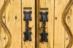Iron door handles. On the yellow wooden doors of a church building Royalty Free Stock Photography