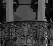 Iron dragon standing on the balcony. Shot in black and white, detail on the sculpture on the facade of this historic building  representing some animals. Set in Stock Photo