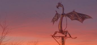 Iron dragon under a cloudy burning sky at sunset royalty free stock photography