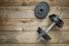 Iron dumbbell. Exercise weights - iron dumbbell with extra plates on a wooden deck Stock Images