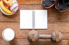 Iron dumbbell,Sports shoes and notebook with milk and fruit (ban Royalty Free Stock Photos