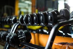 A full set of dumbbells, stuff for effective magnification of power and muscle size on a dark blurred background. Iron dumbbells, equipment for weight lifting Royalty Free Stock Photography