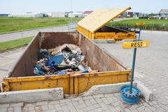 Iron dumpster with groundwood  at a refuse dump Royalty Free Stock Photo