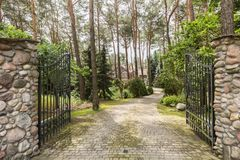 Iron entrance gate and stony road leading to the house in the woods. Concept photo royalty free stock photography
