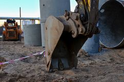 Excavator bucket in the sandy ground, earthworks concept. Iron excavator bucket in the sandy ground, earthworks concept royalty free stock image