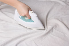 Iron in female hand ironing cotton linen. Iron in female hand ironing wrinkled cotton linen Stock Image