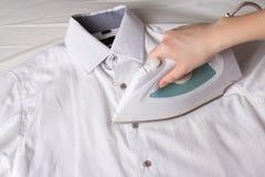 Iron in female hand ironing cotton shirt Stock Photo