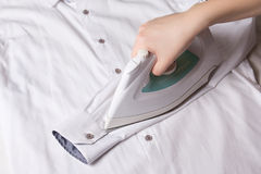 Iron in female hand ironing sleeve of cotton shirt Stock Photo