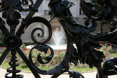 Iron fence. Black iron fence with fountain in background Royalty Free Stock Photo