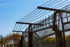 Iron fence with barbed wire. An iron fence with the barbed wire on the background of clear sky Royalty Free Stock Images