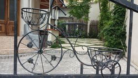 Iron fence - bicycle. Garden fence with a 3 wheels bicycle model. Image taken with smartphone stock photography