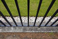 Iron fence, grass and pebbles Royalty Free Stock Images