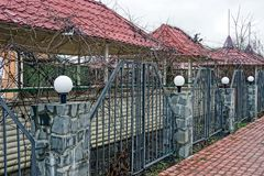 Iron fence with lanterns overgrown with dry vegetation. Part of the fence of iron and stone with white lanterns overgrown with dry branches of plants Royalty Free Stock Photo