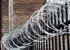 Iron fence with razor and barbed wire Royalty Free Stock Photos