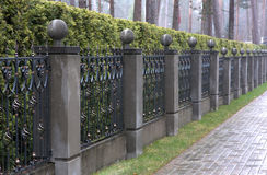 Iron fence with stone pillars Stock Photo