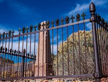 Fleur de lis and angel face head on iron fence guarding a grave royalty free stock image