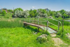 Iron footbridge over small river Royalty Free Stock Photography