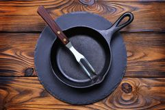 Iron frying pan on a serving board on wooden background. Royalty Free Stock Photography